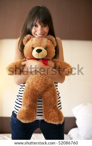 Young woman with teddy bear in bed
