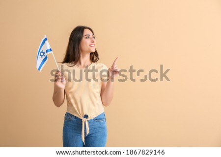 Young woman with the flag of Israel pointing at something on color background Stok fotoğraf ©