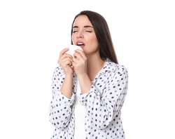 Young woman with tissue sneezing on white background. Runny nose