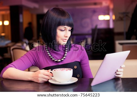 Young woman with touch screen tablet computer in cafe