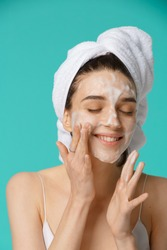 Young woman with towel wrapped around her head applying facial cleaning foam and having fun. Daily routine - face cleaning, skin care, peeling, moisturising and beauty treatment concept