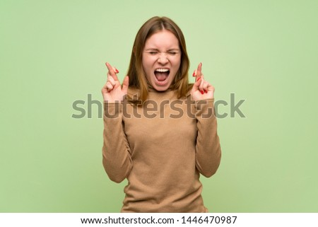 Young woman with turtleneck sweater with fingers crossing #1446470987