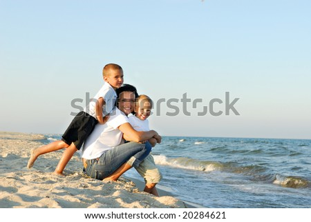 Young woman with two boys on the sand by the ocean.