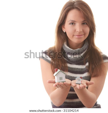 Young woman with two hose models in hands (compering them) isolated on white background - Real Estate loans concept