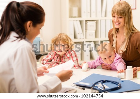 Young woman with two little children girl speak to pediatrician