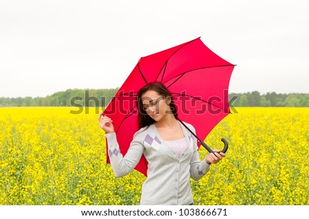 young woman with umbrella in canola field