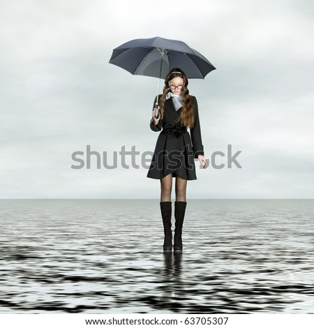 Young woman with umbrella standing on water