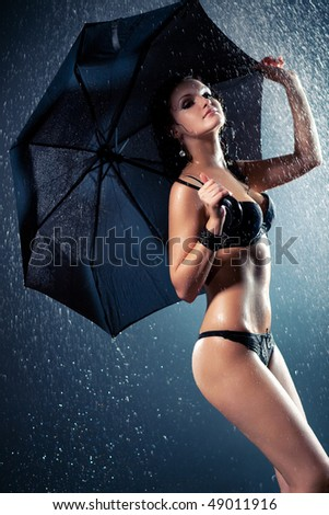 Young woman with umbrella under the rain. Water studio photo.