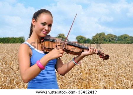 Young woman with violin in crop field