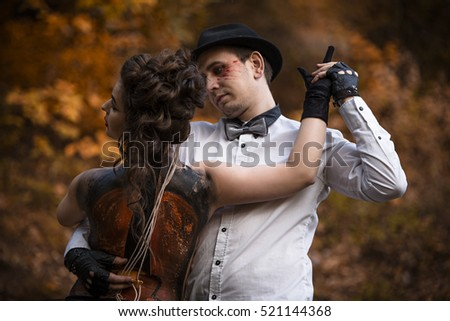 Stock Photo young woman with violin painted on her back held by young man in dancing pose