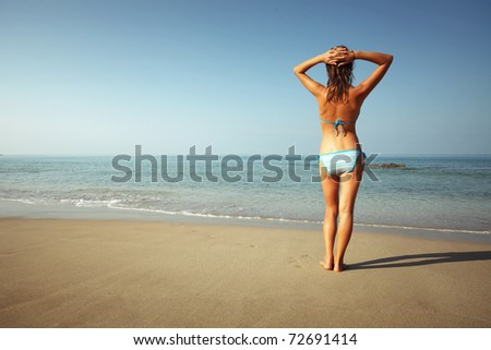 Young woman with wet skin standing on sand and looking to a sea