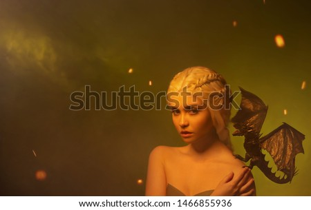 young woman with white braided hair and little dragon on shoulder. hostess of magical beasts with innocent face in fog and sparks of fire, creature of polymer clay, Space for text #1466855936