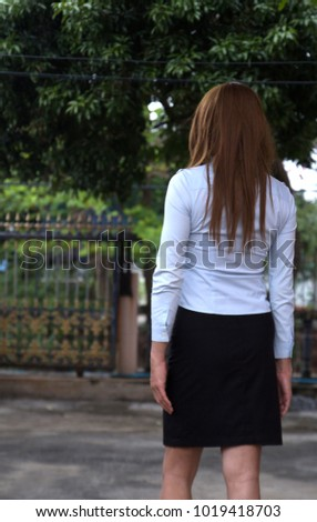 young woman with white long shirt and black skirt relaxing in home, looking at view outside fence with many trees #1019418703