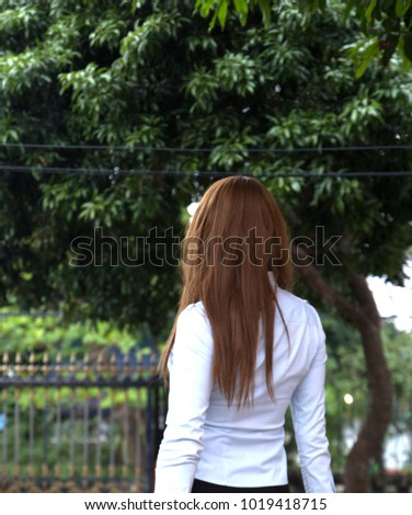 young woman with white long shirt and black skirt relaxing in home, looking at view outside fence with many trees #1019418715