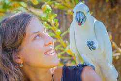 Young woman with white parrot sitting on her shoulder, in  Bali Bird Park, Indonesia