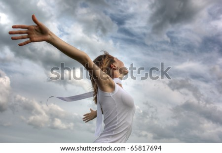 Young woman with white ribbon and raised hands on clouds background