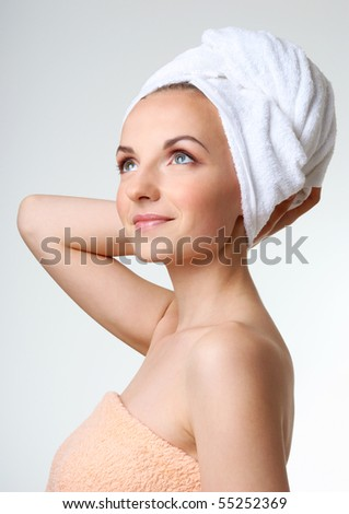 Young woman with white towel on her head. Looking upward.