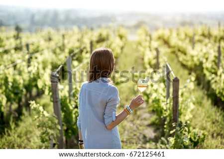 Young woman with wine glass standing on the beautiful vineyard during the sunset