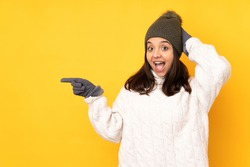 Young woman with winter hat over isolated yellow background surprised and pointing finger to the side