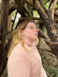 Young woman with worried expression looking upward in densely wooded forest