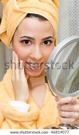 Young woman with yellow towel on head looking  at her face  in the mirror