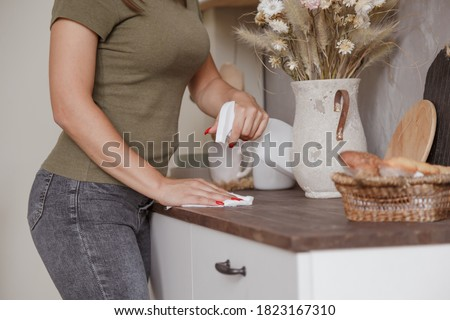 Photo of  Young woman without gloves cleaning table with spray rag in kitchen