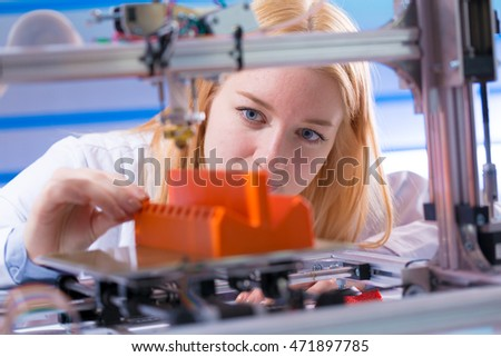 Young woman work with 3d printer #471897785