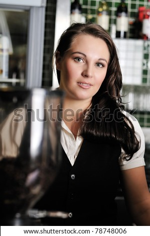 Young woman working as a barista in a coffee shop