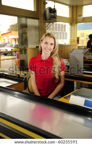 Young woman working as a cashier at the supermarket