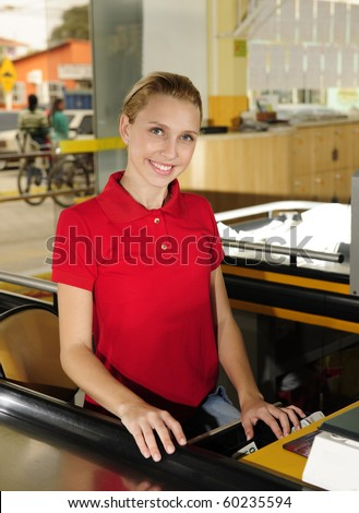 Young woman working as a cashier at the supermarket - stock photo