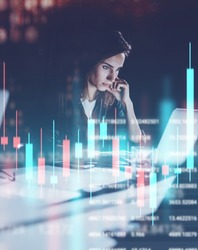 Young woman working at night modern office loft.Red and green candlestick chart and stock trading on background. Double exposure