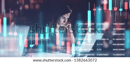 Young woman working at night modern office.Technical price graph and indicator, red and green candlestick chart and stock trading computer screen background. Double exposure.Wide