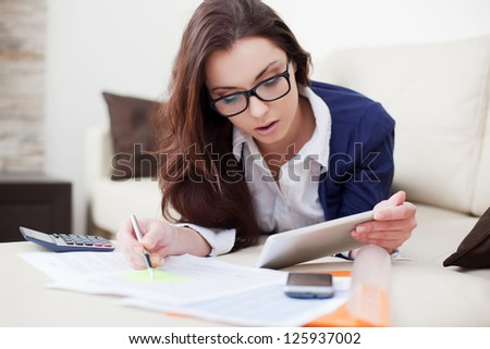 Young woman working from home using her digital tablet