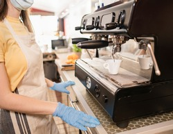 Young woman working in a bar and makes coffee - Caucasian woman wearing protective gloves and face mask at work - Focus on the coffee that runs out of the machine