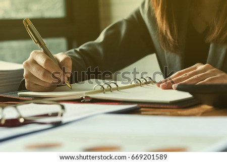 Young woman working in bright office, using laptop, writing notes. #669201589