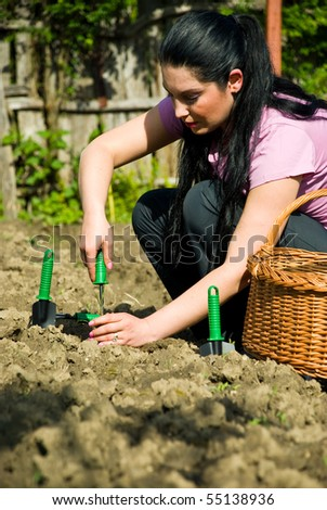 Young woman working in garden and using tools  at countryside
