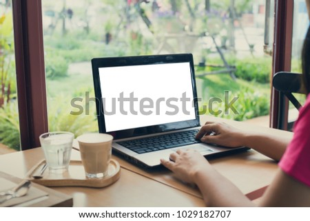young  woman working  laptop computer on wood desk in a coffee shop.,Empty notebook #1029182707