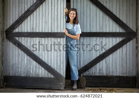 Young woman working on a farm is opening the door of a barn or shed #624872021