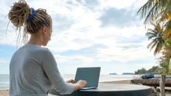 Young woman working on laptop at sand beach of tropical island. Freelance outdoor work concept