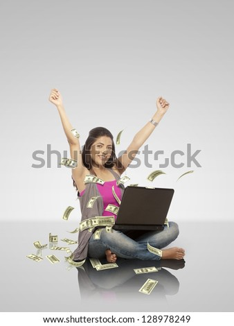 young woman working on laptop from which dollar note is coming out