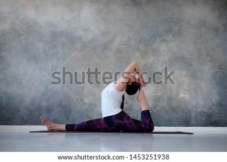 Young woman working out, doing yoga or pilates exercise. Monkey god, splits, hanumanasana.