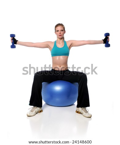 Young woman working out with dumbbells on a fitness ball