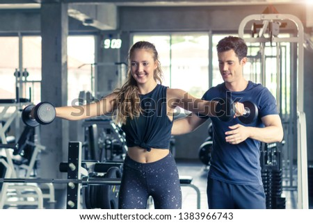 Young woman working out with fitness trainer at the gym club.