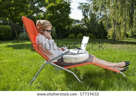 young woman working outside on computer, in the garden