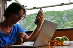 Young woman working with laptop computer on the table in camper van with mountain scenic view through the window