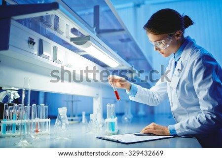 Young woman working with liquids in glassware