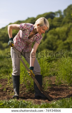 Young woman working with shovel on the garden outdoor