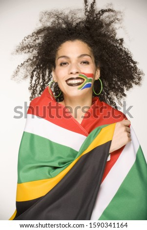 Young woman wrapped in South African flag