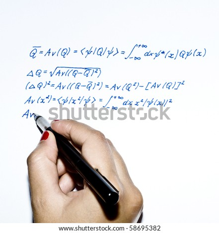 Young woman writing a physical formula with pen