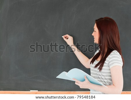 Young woman writing on a blackboard holding her notes in a classroom